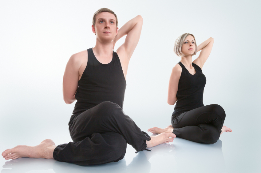 Young man and woman doing yoga in gomukhasana cow face pose