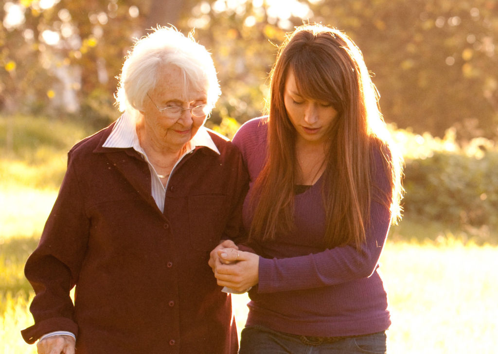Young Woman helping Older Women walk in woods