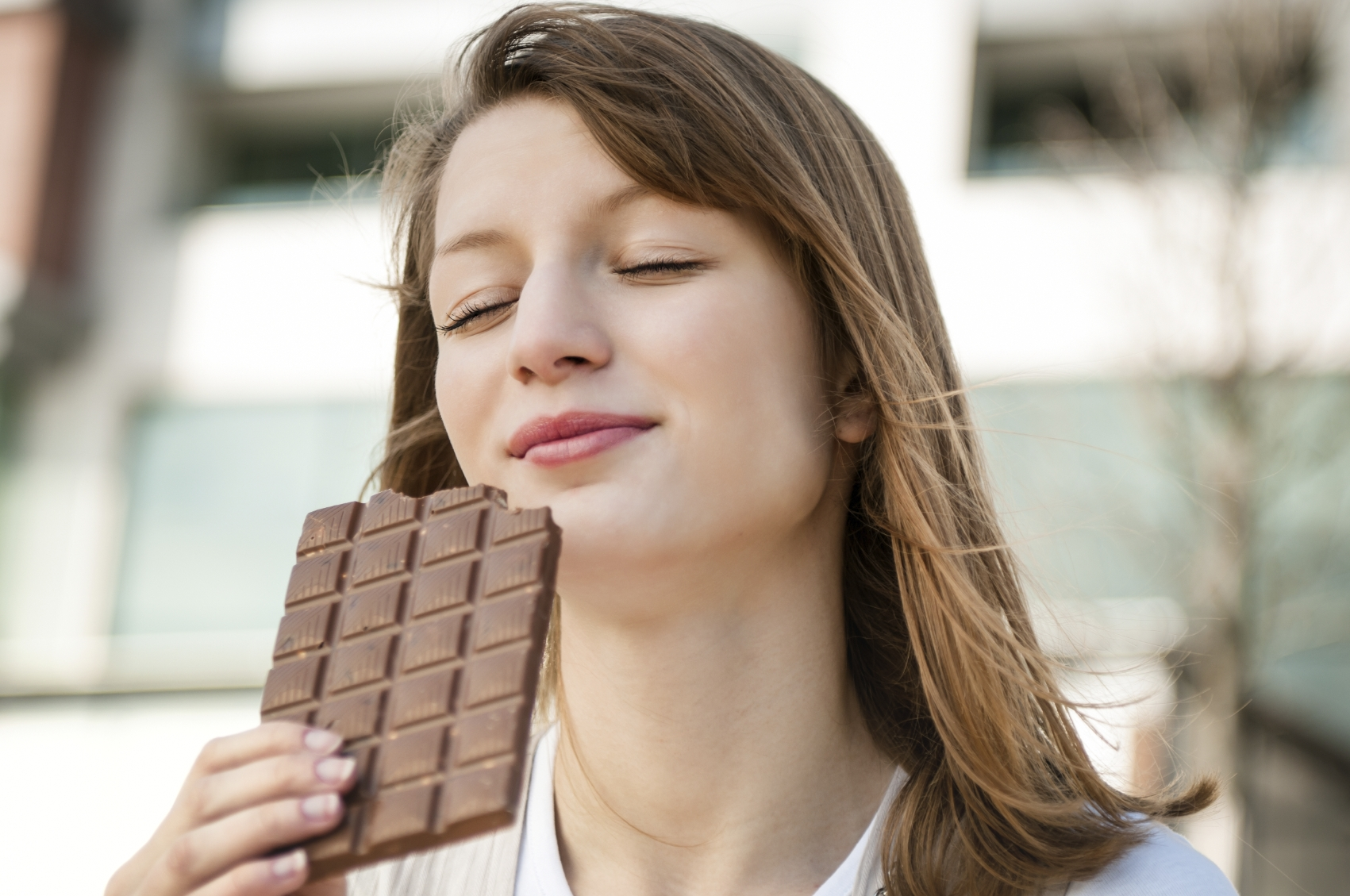Portrait of young beautiful woman eating chocolate - lifestyle outdoor image