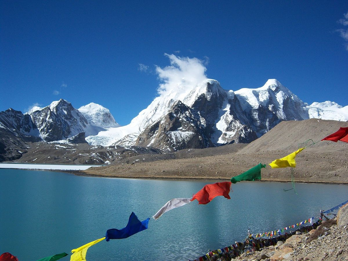 1200px-Buddhist_Flag_flutters_in_GuruDongmar_Lake