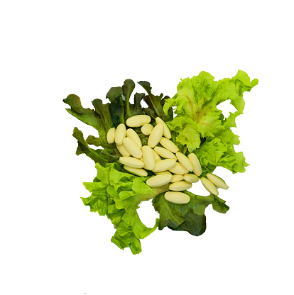 Yellow big tablets or pills on  vegetables on isolated white background in health care concept